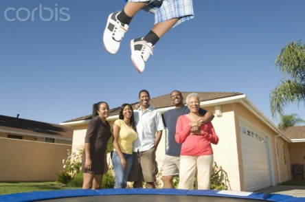 Family watching boy jumping on trampoline
