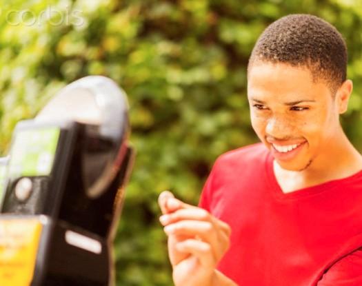 19 Jun 2014 --- African American man paying parking meter --- Image by © JGI/Daniel Grill/Blend Images/Corbis